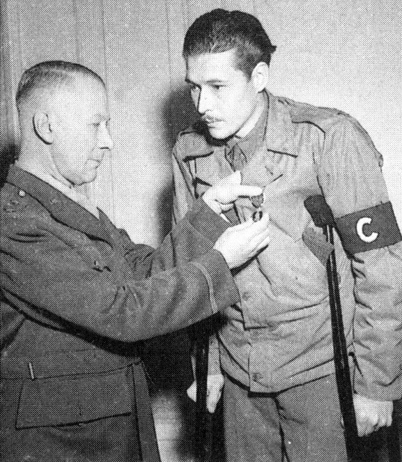 "Major General Lloyd R. Fredendall, who later commanded the U.S. II Corps in Tunisia, pins a Purple Heart on correspondent Leo ""Bill"" Disher."