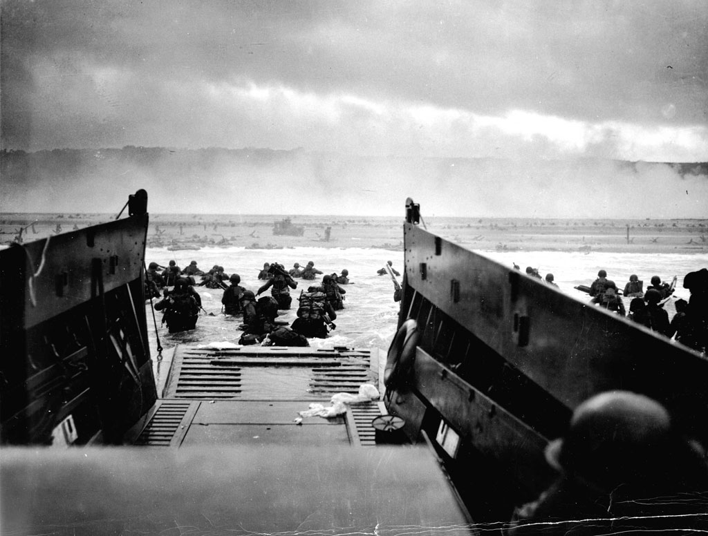 American soldiers wade from a landing craft toward Omaha Beach and the bluffs beyond on the morning of June 6, 1944.