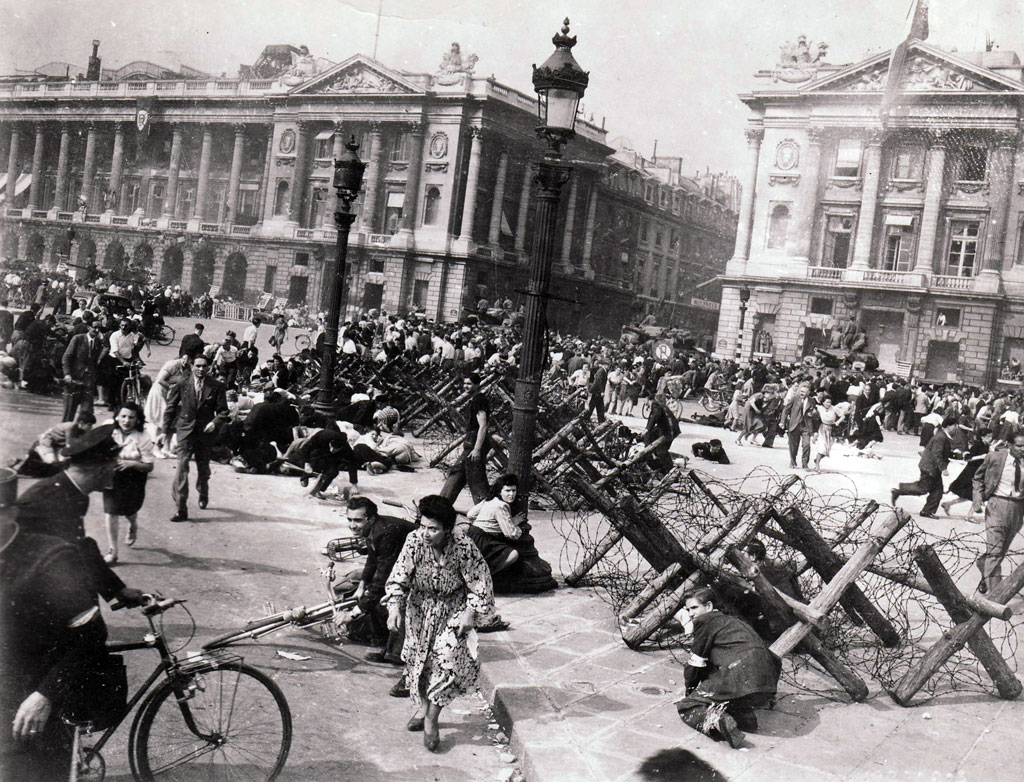 Sniper fire sends French citizens sprawling or fleeing in the Place de la Concorde on August 26, 1944.