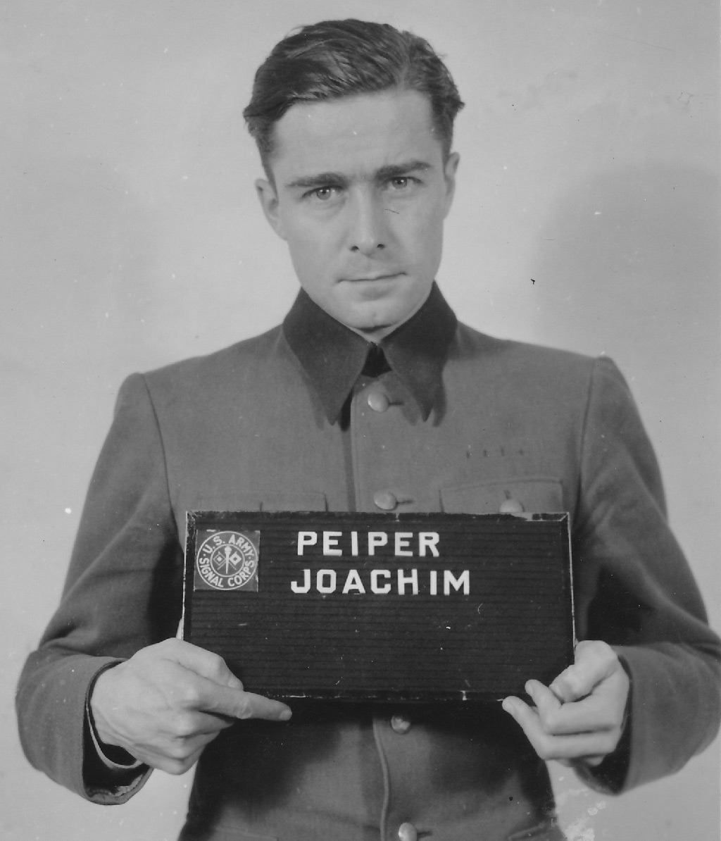 Lieutenant Colonel Joachim Peiper led a vanguard of six thousand SS troops across Belgium in a vain effort to seize crossings on the Meuse river. Convicted of mass murder, he would be condemned to death but his sentence was commuted.